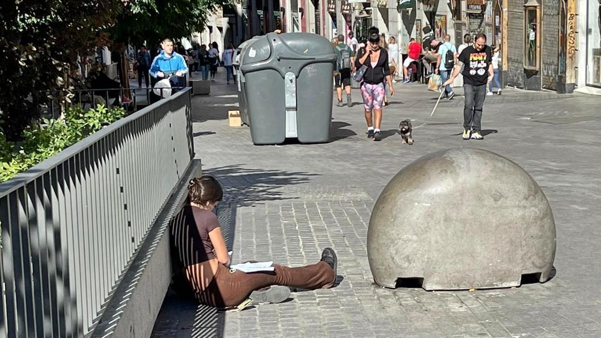 Joven sentada en el suelo con apuntes, en el lugar de Carretas donde se ha vallado el banco corrido
