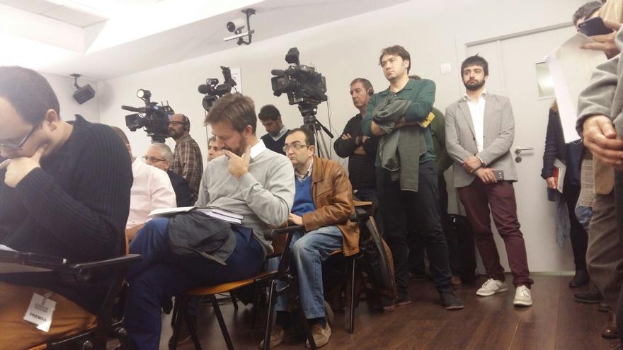 El gerente del club náutico de Xàbia, Luis Nogueroles, sentado con barba y jersey gris, asiste a la rueda de prensa en la que Mònica Oltra fue preguntada sobre los puertos deportivos.