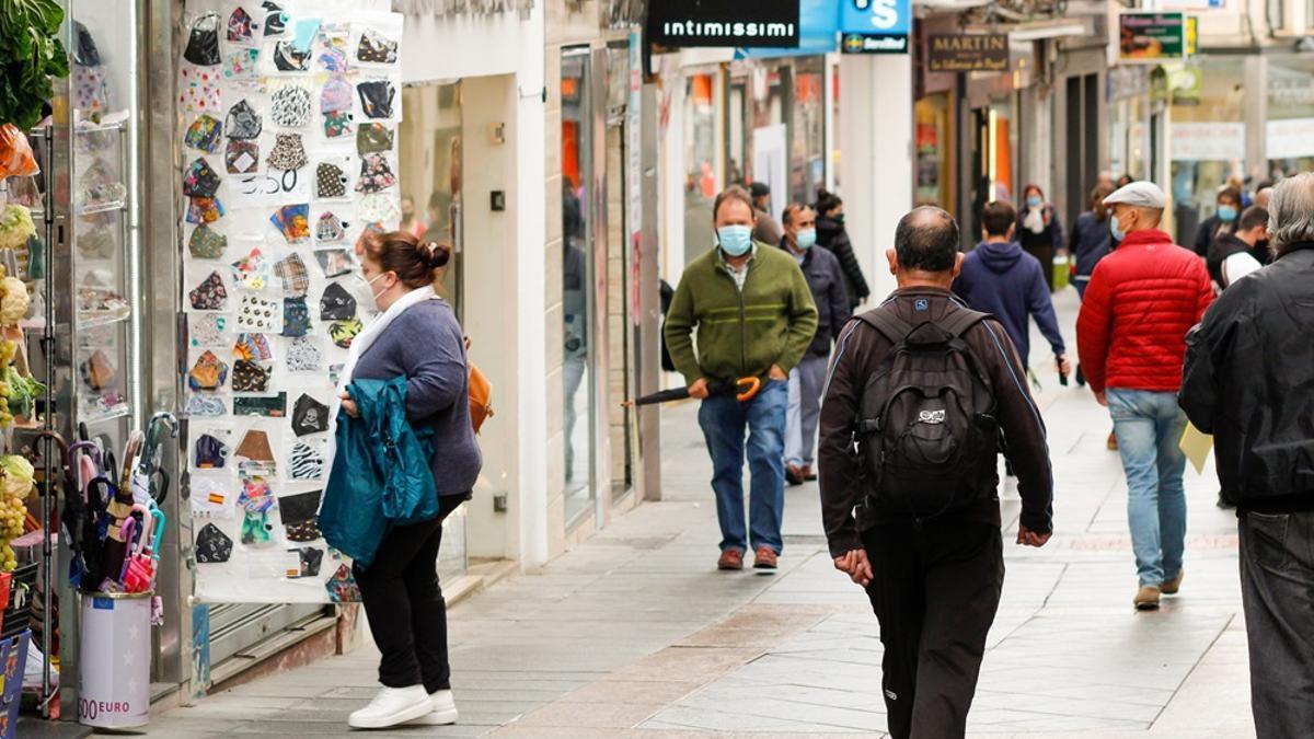 Varias personas pasean con mascarilla por una calle comercial