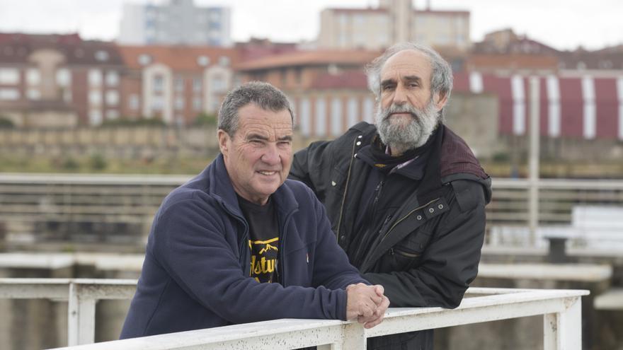 Los sindicalistas Cándido y Morala con los terrenos del antiguo astillero de Naval Gijón al fondo