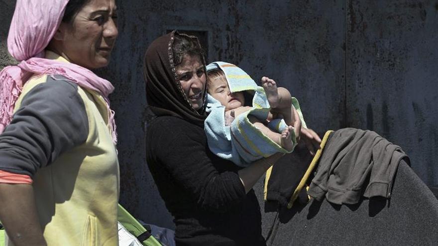 Una mujer sostiene a su bebé en brazos junto a una tienda de campaña en el Puerto del Pireo en Grecia este 31 de marzo.