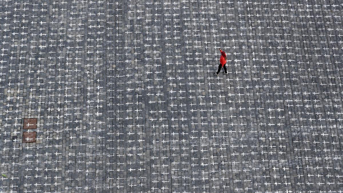 Marzo de 2021. Una mujer camina por la Old Town Square de Praga, República Checa, donde miles de cruces pintadas conmemoran el primer aniversario de la primera muerte en el país por coronavirus.