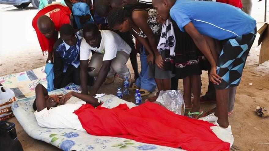 Un superviviente del ataque perpetrado contra la Universidad de Garissa habla con otros estudiantes mientras aguardan en el campamento militar de Garissa, al este de Kenia
