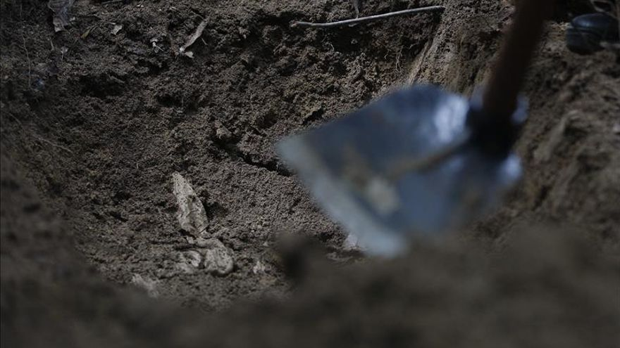 Un equipo de la policía forense malasia exhuma restos humanos de una fosa descubierta en las colinas Wang Burma en Wang Kelian, Perlis (Malasia).