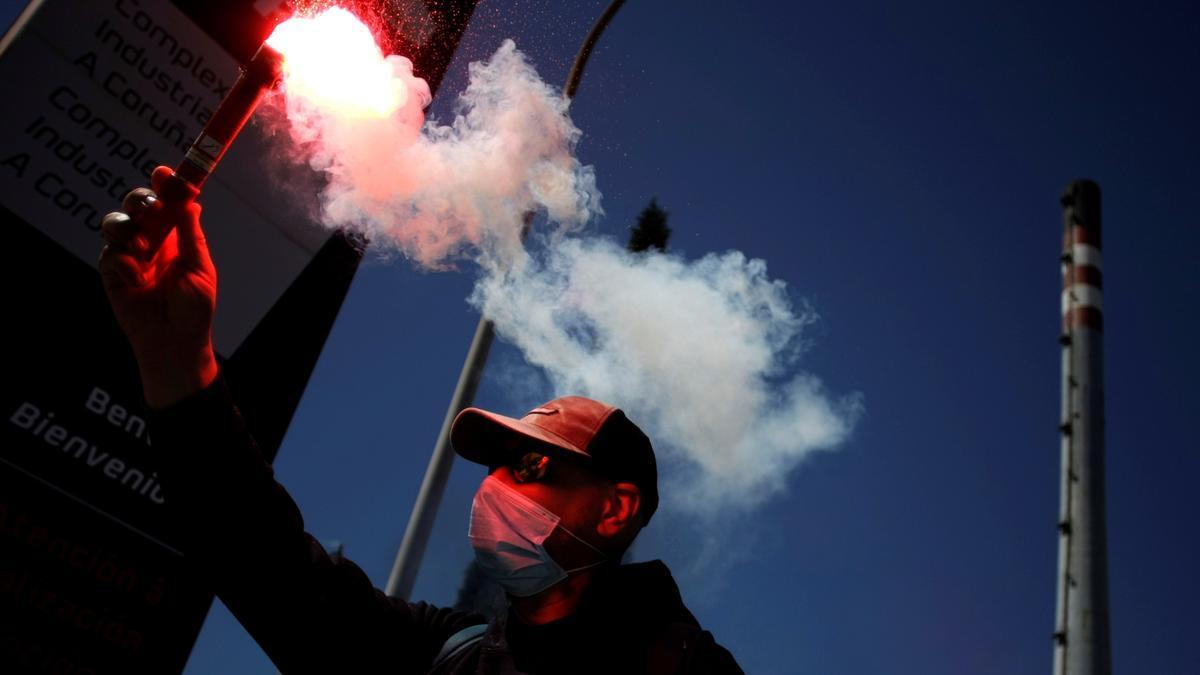 Un trabajador de la refinería Repsol de A Coruña ondeaba una bengala durante la manifestación convocada por el comité de empresa.