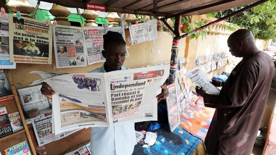 Varios hombres leen los titulares en los diarios de un quiosco en Bamako (Mali).
