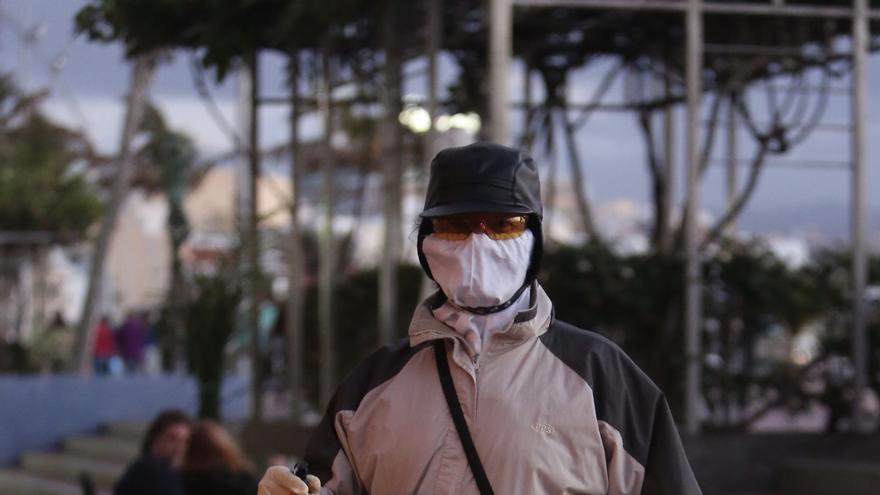 Un hombre con una mascarilla y desinfectante durante la pandemia de COVID-19.
