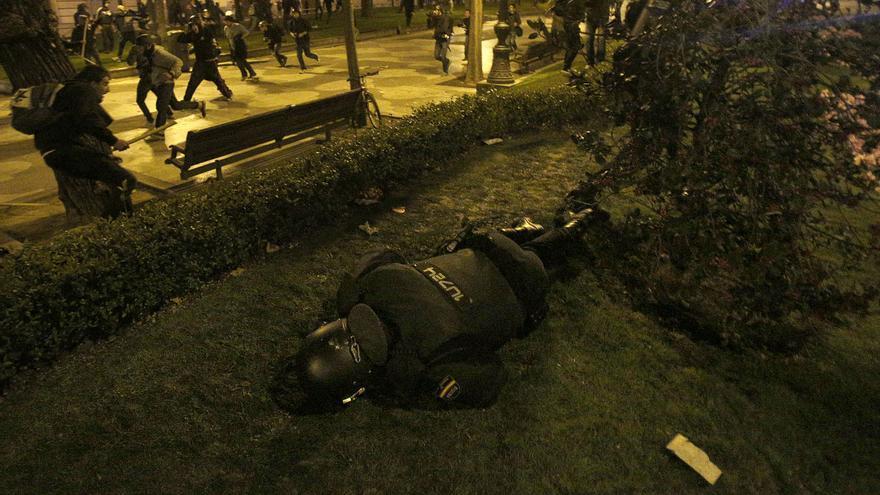 Un agente de la Policía Nacional, tendido en el suelo tras recibir el impacto de un objeto / Olmo Calvo