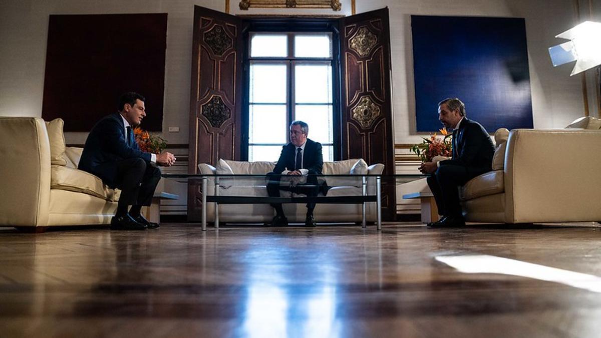 El presidente andaluz, Juan Manuel Moreno (PP), conversa con el secretario general del PSOE-A, Juan Espadas, y con el consejero de Hacienda, Juan Bravo, en el Palacio de San Telmo.