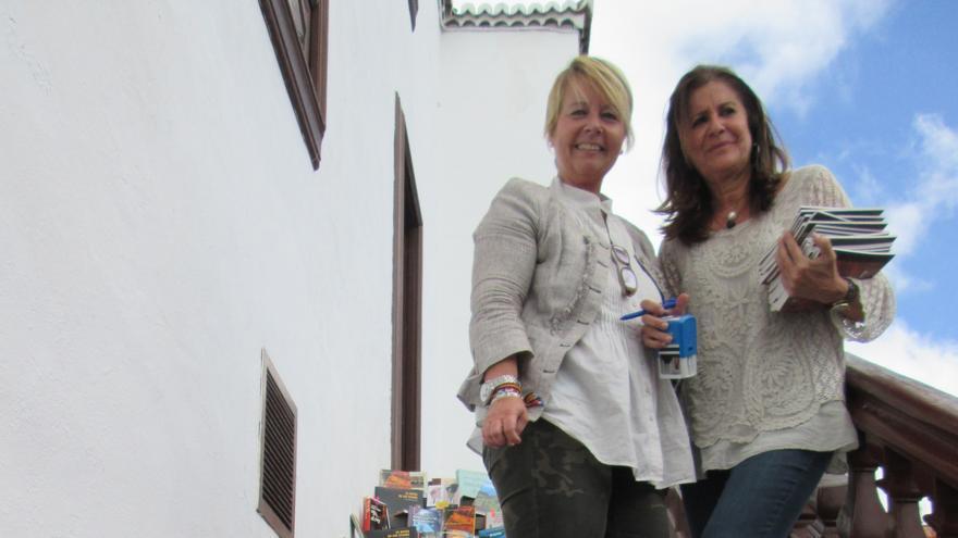 Rosa Aguado y Mari Carmen Aguilar en las escaleras repletas de libros.