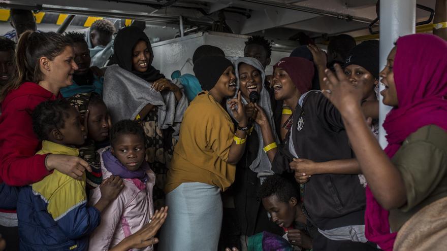 Un grupo de mujeres cantando con un altavoz instalado por los voluntarios de Proactiva Open Arms en la cubierta del barco. Decenas de mujeres, niños y hombres se animaron a participar en la actividad / Olmo Calvo