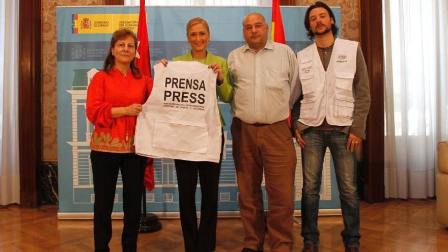 Cristina Cifuentes y la presidenta de la FAPE, Elsa González, presentando el chaleco de prensa optativo para periodistas asociados