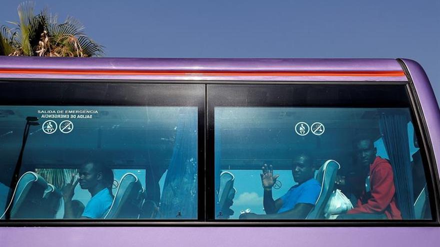 Algunos de los 78 migrantes, que llegaron a Valencia en el barco Aquarius, y que han decidido marcharse a Francia, saludan desde el autobús esta mañana a su llegada al aeropuerto de Manises para volar en un charter fletado por la entidad Organización Internacional para las Migraciones.