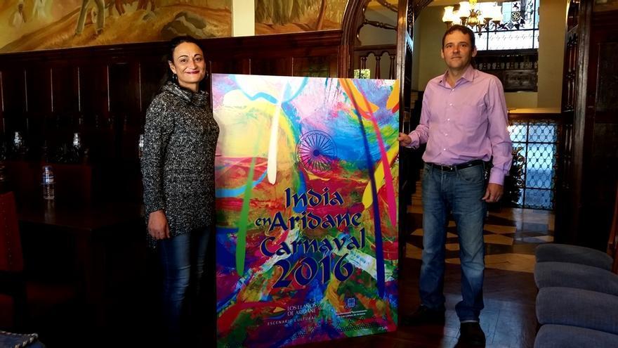 La concejal de Fiestas y el autor del cartel muestran la obra.