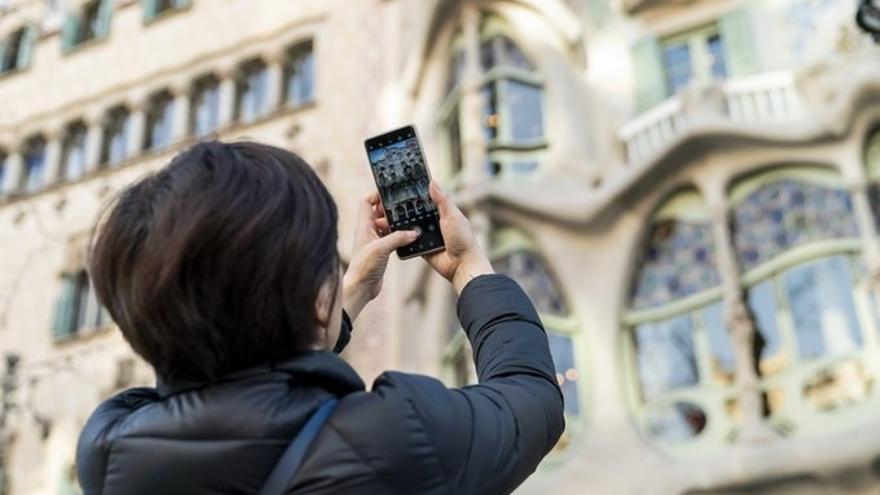 Una turista realiza una fotografía con su teléfono móvil a la Casa Batlló de Barcelona