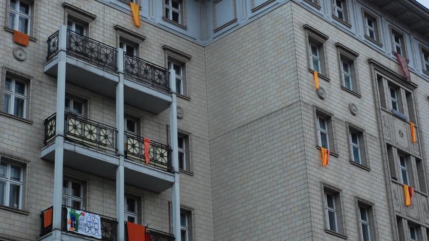 """Pancartas y lazos rojos y naranjas que simulan """"un incendio"""" como protesta en los edificios de Karl Marx Allee, en Berlín."""