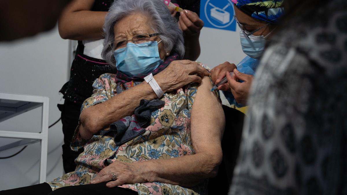 Leonila González, de 96 años, recibe una dosis de la vacuna Sinovac por parte de un personal sanitario en el primer día de vacunación masiva, en un centro de vacunación montado en el Estadio Bicentenario.