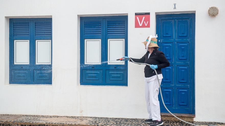 Una vecina de la isla de La Graciosa limpia la fachada de una vivienda vacacional este lunes, primer día de la fase 2 de la desescalada.