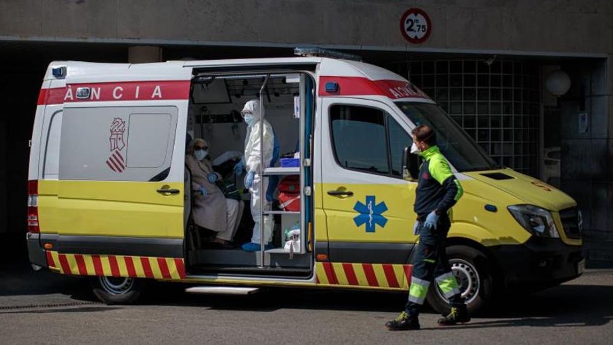 Un sanitario con un equipo de protección integral (EPI), traslada en ambulancia a un paciente al Hospital Clínico de València.