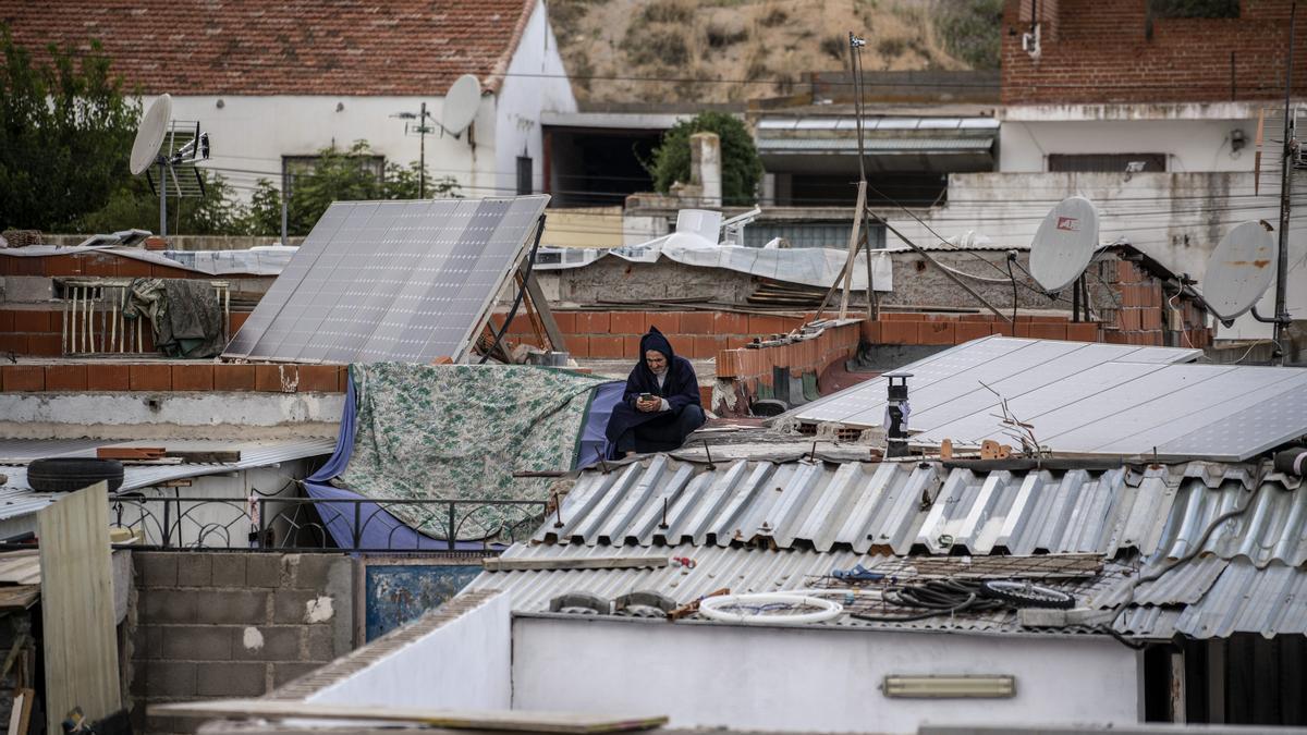 Un hombre mira su móvil rodeado de paneles solares instalados en los tejados de las casas bajas de la Cañada Real.