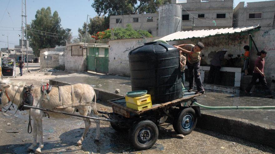 Un niño en Gaza con un tanque de agua