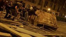 Manifestantes arrastran un contenedor en Barcelona.