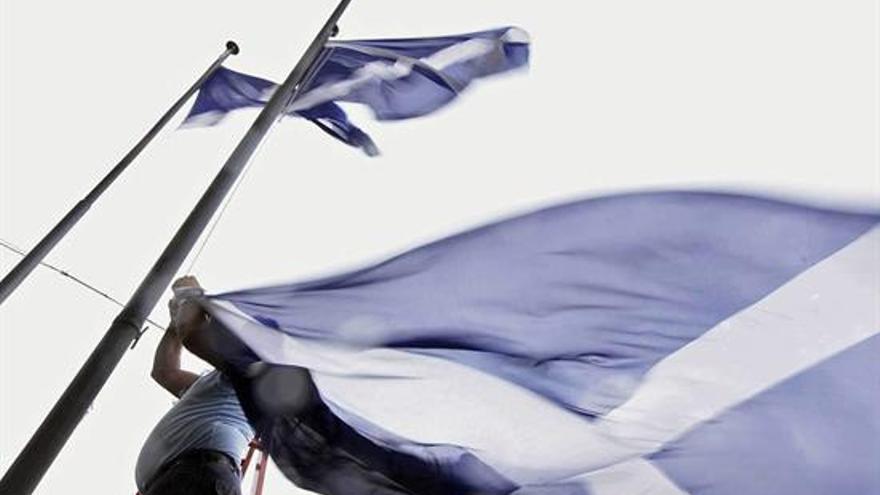 Un operario retira las banderas de Tenerife que habitualmente ondean en el Cabildo insular. EFE/Ramón de la Rocha