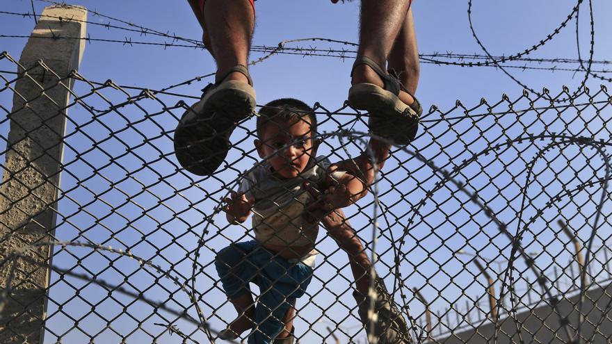 Ayudan a cruzar la valla que divide Siria y Turquía a un niño, al que llevan en volandas al lado turco en la zona de Akcakale, este 14 de junio. / (AP Photo/Lefteris Pitarakis).