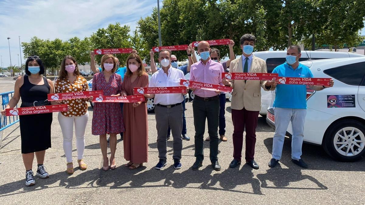 Botella y Ruano (centro) muestran, junto a responsables del hospital y de Pide Taxi, las pegatinas a favor de la donación de órganos.