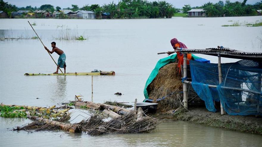 Una pareja busca sus pertenencias tras las inundaciones en el distrito de Morigaon, en Assam (India).