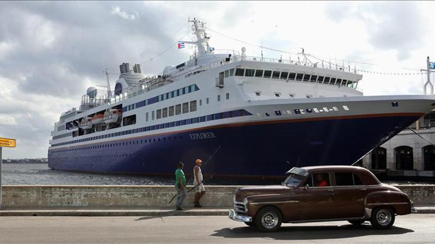 """Un viejo auto pasa junto al crucero académico """"M.V. Explorer"""", fondeado en La Habana (Cuba)."""
