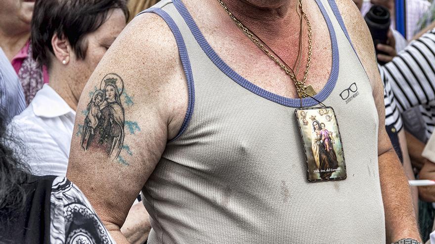 Uno de los participantes (con un tatuaje y un escapulario de La Virgen) en la procesión de El Carmen, que tiene lugar en el Barrio Pesquero de Santander con motivo de su festividad. | ROMÁN GARCÍA (16/07/2014)