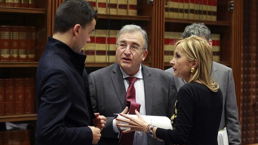 El presidente de la Audiencia de Cuentas de Canarias, Rafael Díaz (c), conversa con los diputados María Australia Navarro y Héctor Gómez (i). EFE