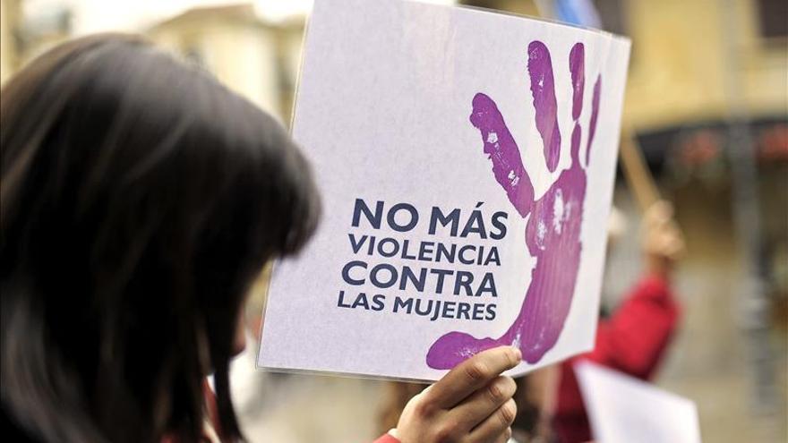 Una mujer camina junto a un cartel contra la violencia de género durante una manifestación.