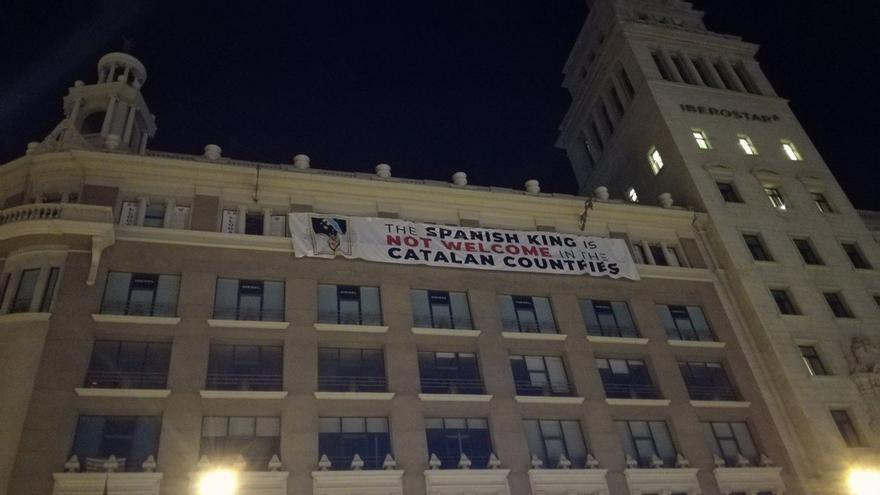 La pancarta en contra de la presencia del rey colocada en uno de los edificio de plaza Catalunya