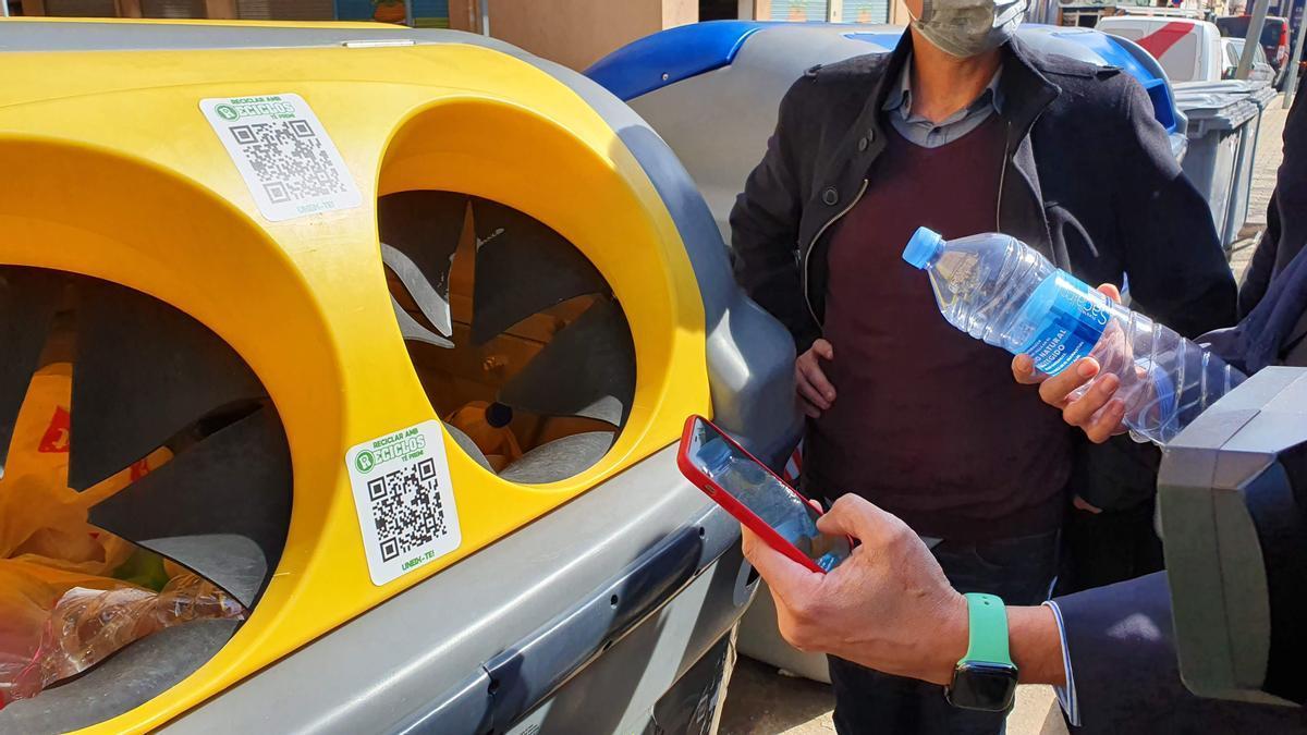 Una persona escanea el código QR para obtener incentivos por reciclar.