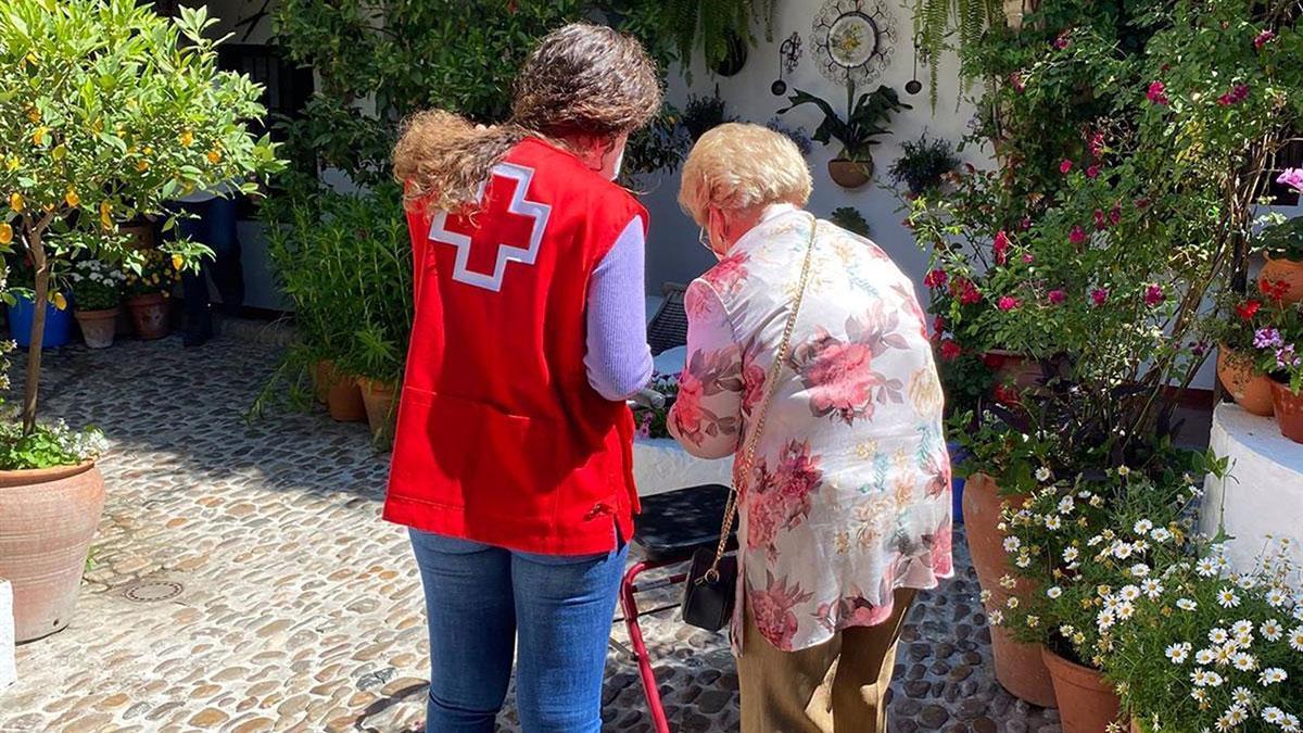Una persona mayor visita un patio en compañía de una voluntaria de Cruz Roja.
