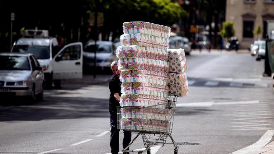Un trabajador transporta numerosos rollos de papel higiénico en un carro de la compra dirección a un comercio en el centro de Málaga.