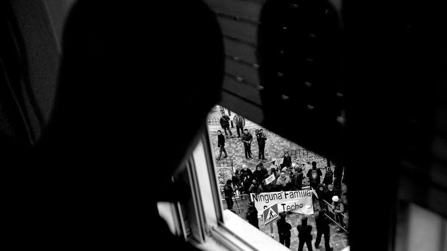 Un hombre observa por la ventana el despliegue policial y la concentración de protesta organizadas antes de su desahucio