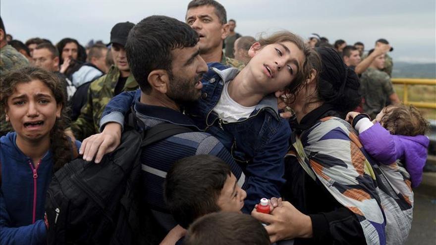 Refugiados intentan pasar una barrera de policías para subir hoy a un autobús en Gevgelija en Macedonia.