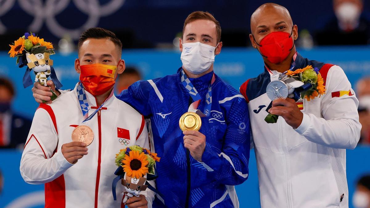 El israelí Artem Dolgopyat (c-oro), el español Rayderley Zapata (d-plata) y el chino Ruoteng Xiao (i-bronce) celebran en el podio tras la final individual de suelo masculino de Gimnasia Artística . EFE/ Enric Fontcuberta