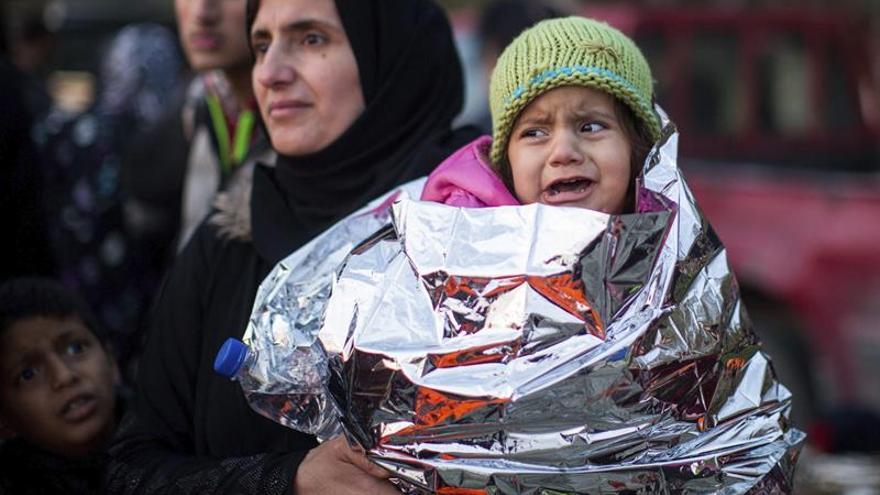 Una niña llora en brazos de su madre al llegar a la isla de Lesbos tras cruzar el mar desde Turquía en el puerto de Mytilene (Grecia) este 9 de marzo.