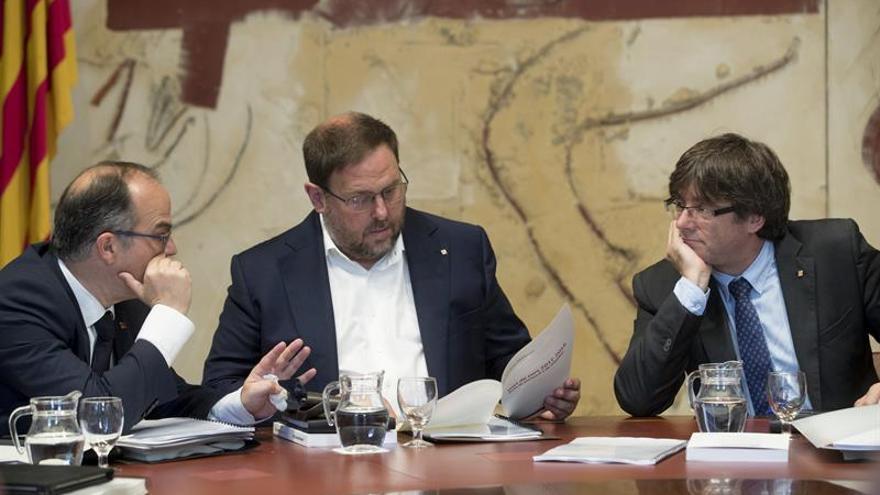 El presidente de la Generalitat, Carles Puigdemont (d), junto al vicepresidente y conseller de Economía, Oriol Junqueras (c), y el conseller de la Presidencia, Jordi Turull (i).