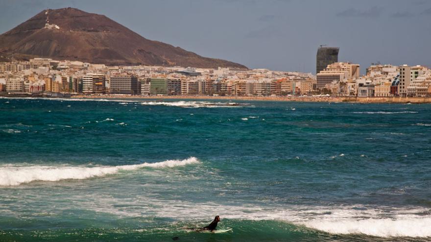 Joven surfeando en las Canteras con la ciudad al fondo.