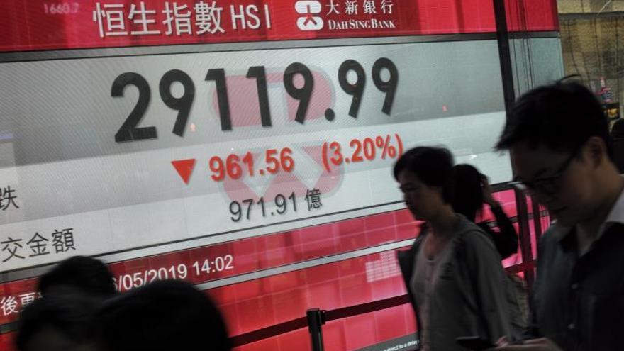 Peatones caminan junto a una pantalla que muestra información bursátil en Hong Kong (China).