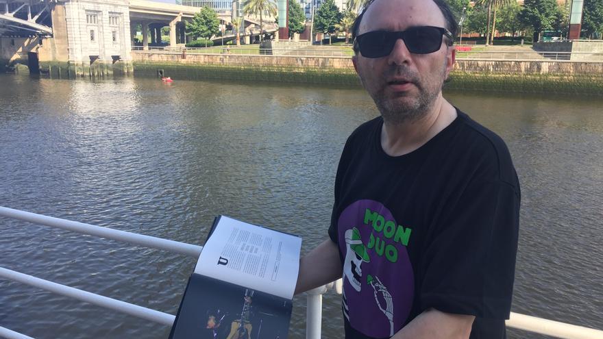 Jerry Corral, con el libro sobre los 15 años del Azkena Rock Festival, junto a la Ría de Bilbao.