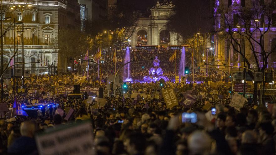 La diosa Cibeles, también iluminada de violeta, y la Puerta de Alcalá, al fondo, muestran una imagen singular entre la riada de manifestantes