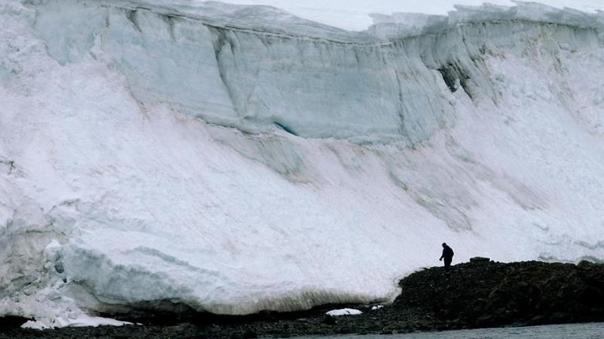 Un hombre camina al borde de un glaciar en la Isla Rey Jorge, en la Antártida uruguaya.
