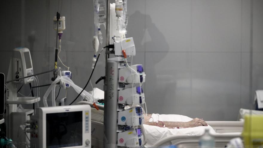 Archivo - Mano de un enfermo con vía subcutánea en una cama de la UCI.