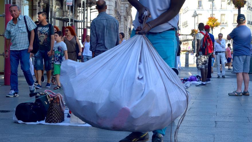 Abdou recoge su mercancía ante la presencia de la Policía   FOTO: P.R.